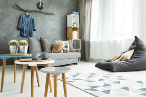 Modern minimalistic and bright living room in shades of cyan with sofa, bean bag chair, three coffee tables, carpet and stillage made of wooden cases