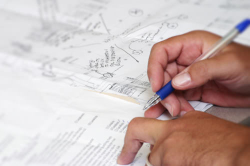 Closeup photo of man working on architectural project, going over check list.